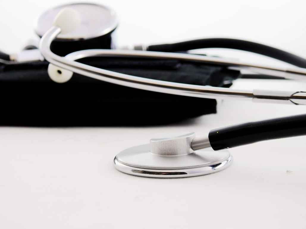 black and silver stethoscope resting on a table