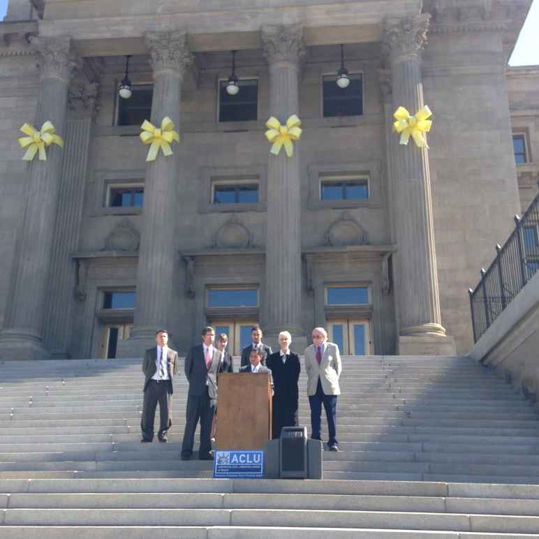Podium on Idaho state capitol steps with people standing behind speaker at podium